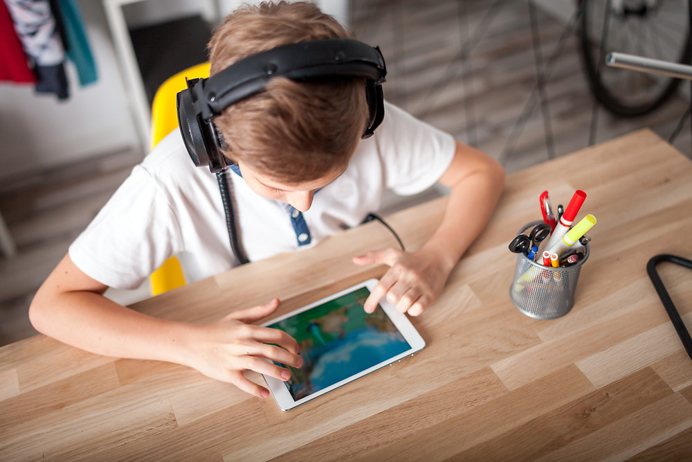 boy learning through play with online games at home on an ipad