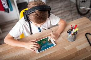 boy looking at ipad wearing headphones wsdc