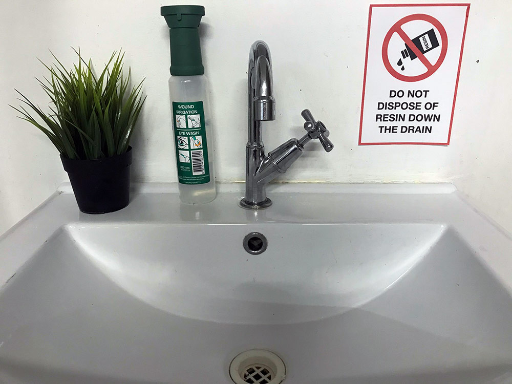 Safety signs near the drain to remind everyone to dispose of resin correctly and not down the drain