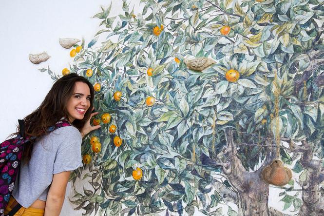 Young Spanish girl pretending to pick an orange