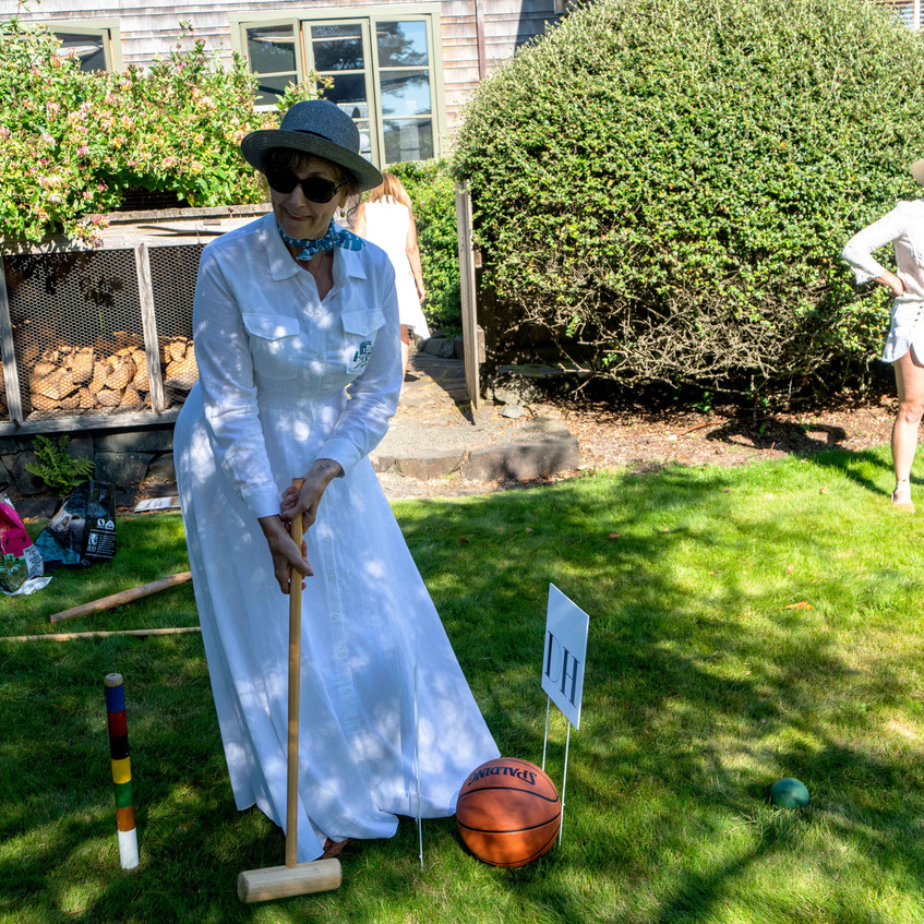 Suzanne Birch or birch community services takes the first shot at the Daniel House croquet classic supporting portland non-profits, portland design