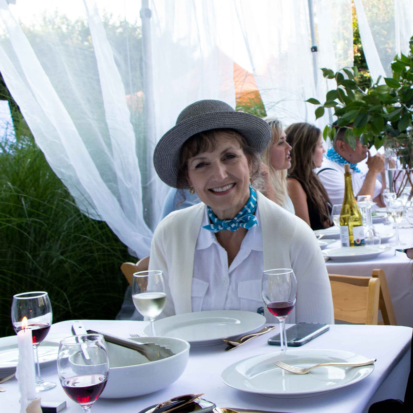 Suzanne Birch in croquet whites eating dinner in the croquet tent designed by Daniel House for the croquet classic