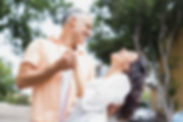 Cheerful couple dancing against trees in