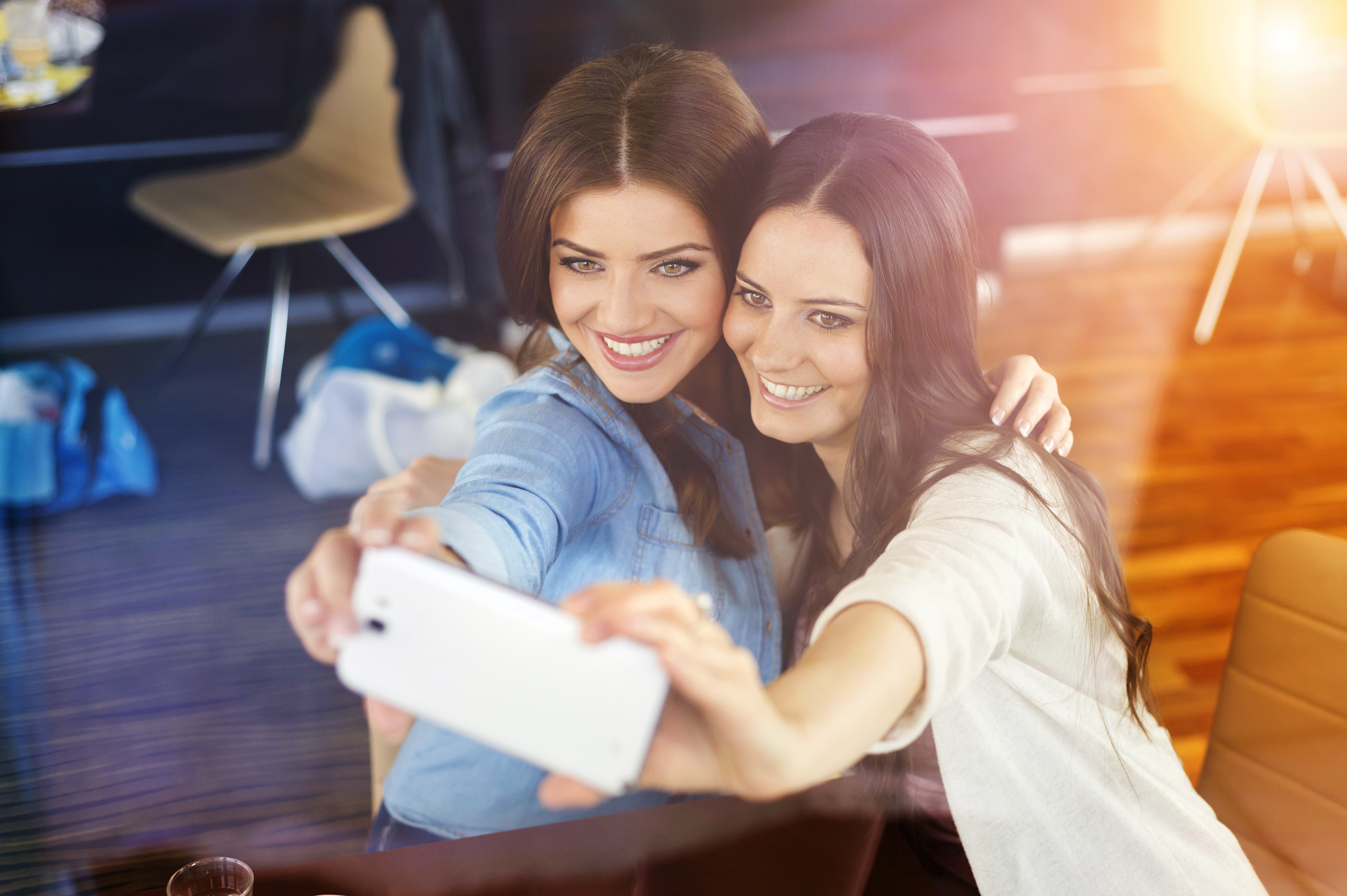 graphicstock-two-beautiful-women-taking-selfie-in-cafe_SAWO3da-W