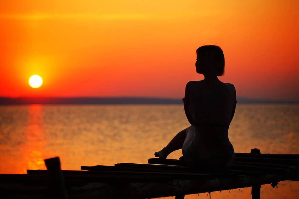 silhouette-of-woman-sitting-on-dock-duri