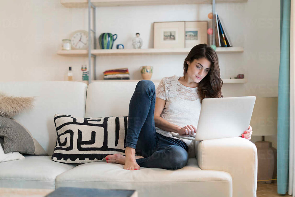 woman-sitting-on-couch-at-home-using-lap
