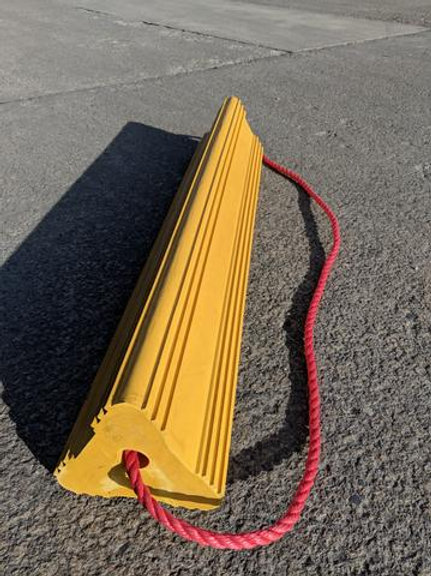 long yellow aircraft wheel chock on concrete floor with red rope running through it