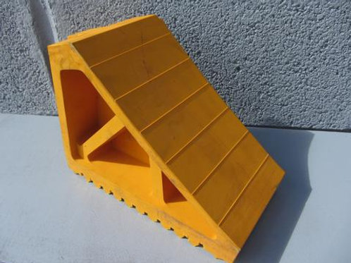 yellow rubber handled wheel chock in front of a concrete wall