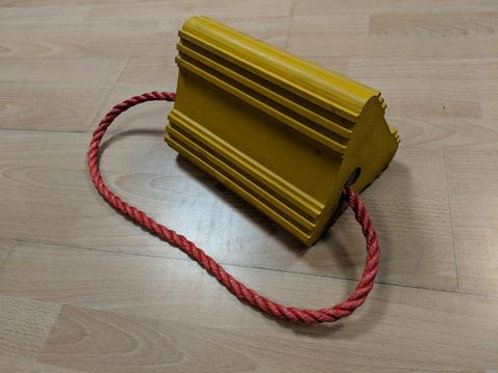 Yellow aircraft wheel chock with red rope on wooden floor