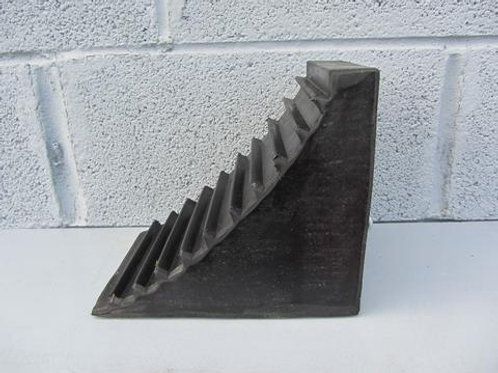 side view of black wheel chock on a shelf in front of concrete wall