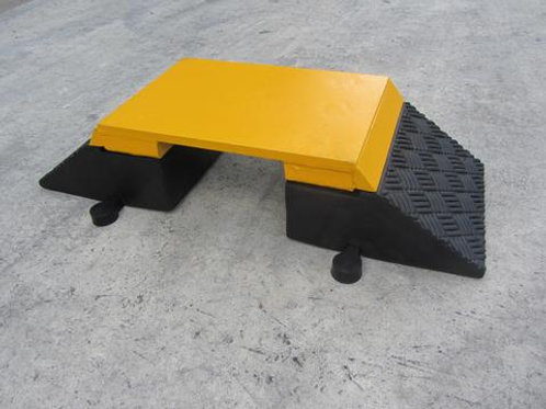 Black and yellow hose and cable ramp on a concrete floor