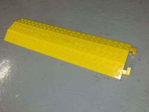 yellow hose and cable ramp on warehouse floor
