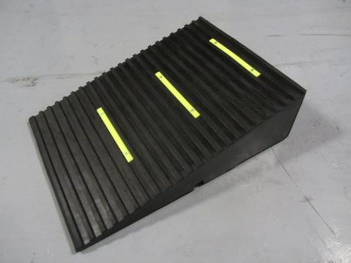 black rubber hose and cable ramp with yellow chevrons on concrete floor