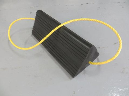 black aircraft wheel chock with yellow rope running through on warehouse floor
