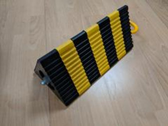 black and yellow aircraft wheel chock on wooden floor