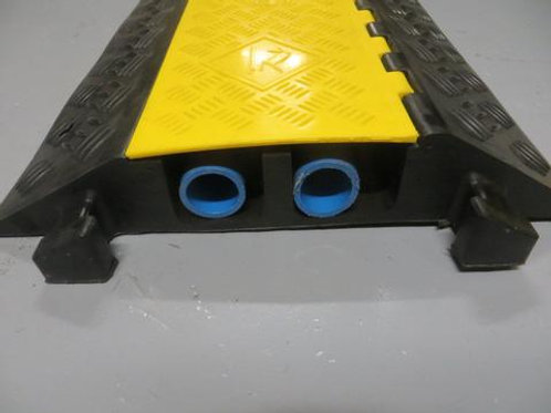 black and yellow hose and cable ramp on warehouse floor