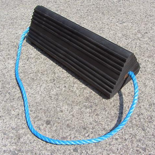 black rubber aircraft wheel chock with blue rope running through it on concrete floor