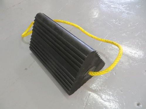 black rubber aircraft wheel chock with yellow rope handle running through it