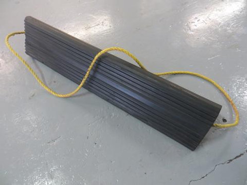 long black rubber aircraft wheel chock with yellow rope handle on warehouse floor