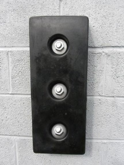 black rubber dock bumper on brick wall