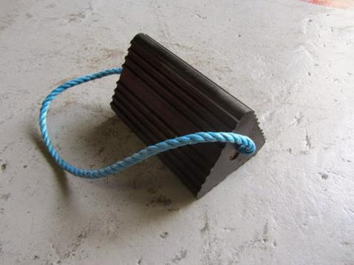 black wheel chock on a concrete floor with blue rope