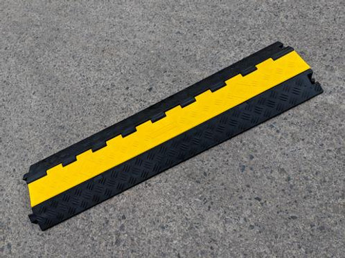 black and yellow hose and cable ramp on concrete floor