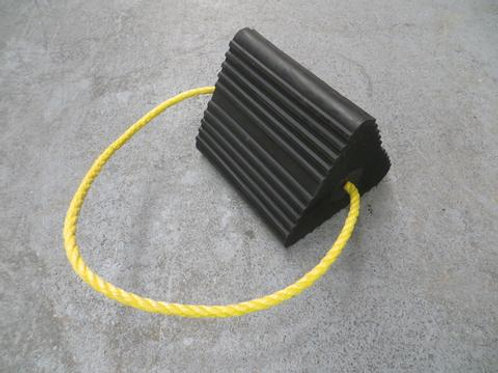 black aircraft wheel chock with yellow rope handle on warehouse floor