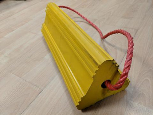 yellow aircraft wheel chock with red rope running through it on wooden floor