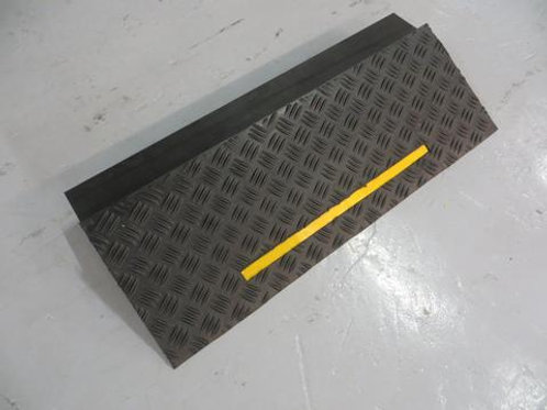 black rubber kerb with yellow strip on concrete floor