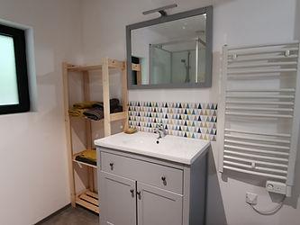 Salle d'eau avec meuble vasque, miroir, sèche-serviette et rangement