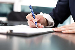 a close up of a persons hand with pen signing a document