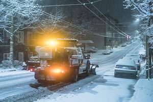 snow truck working at night on snowy day