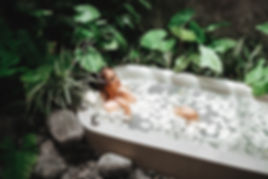 Woman relaxing in round outdoor bath wit