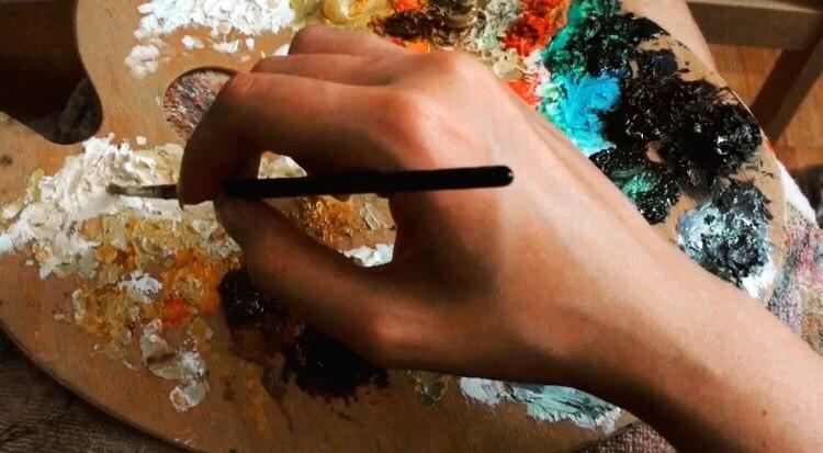 Hand holding a paint brush, palette, oil paints, mixture of paint, mediums