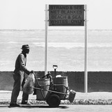 A cleaner walks past a whites only beach sign.