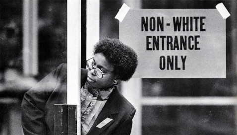 A black female worker peers out from a segreagated entry to an office building.