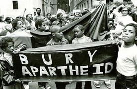 Bury Apartheid bannwr held oaloft by young children.