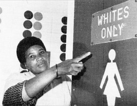 A black woman points to a segregated toilet sign.