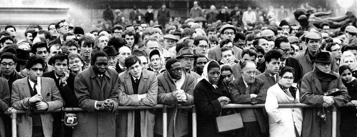 Large crowd of anti-apartheid protestors listening to a speaker at a rally in the 1960's.