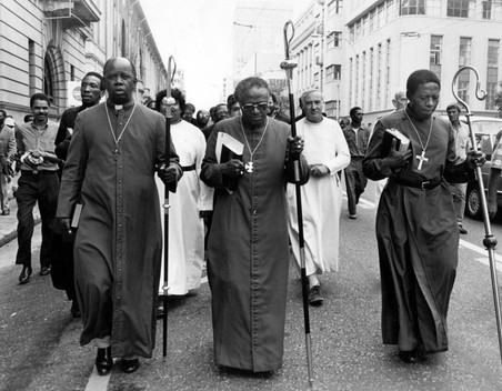 Anti-apartheid campaigner Archbishop Desmond Tutu marches in the streets of Cape Town with other clergy. A major force in the struggle he won the Nobel Peace Prize in 1984.