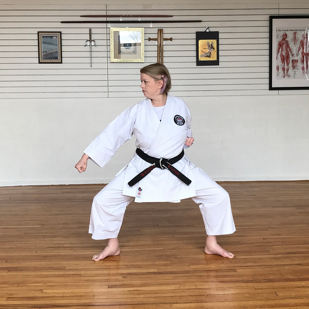 Sensei Barb performing a low block in shake dachi. Ankles are visibly swollen.