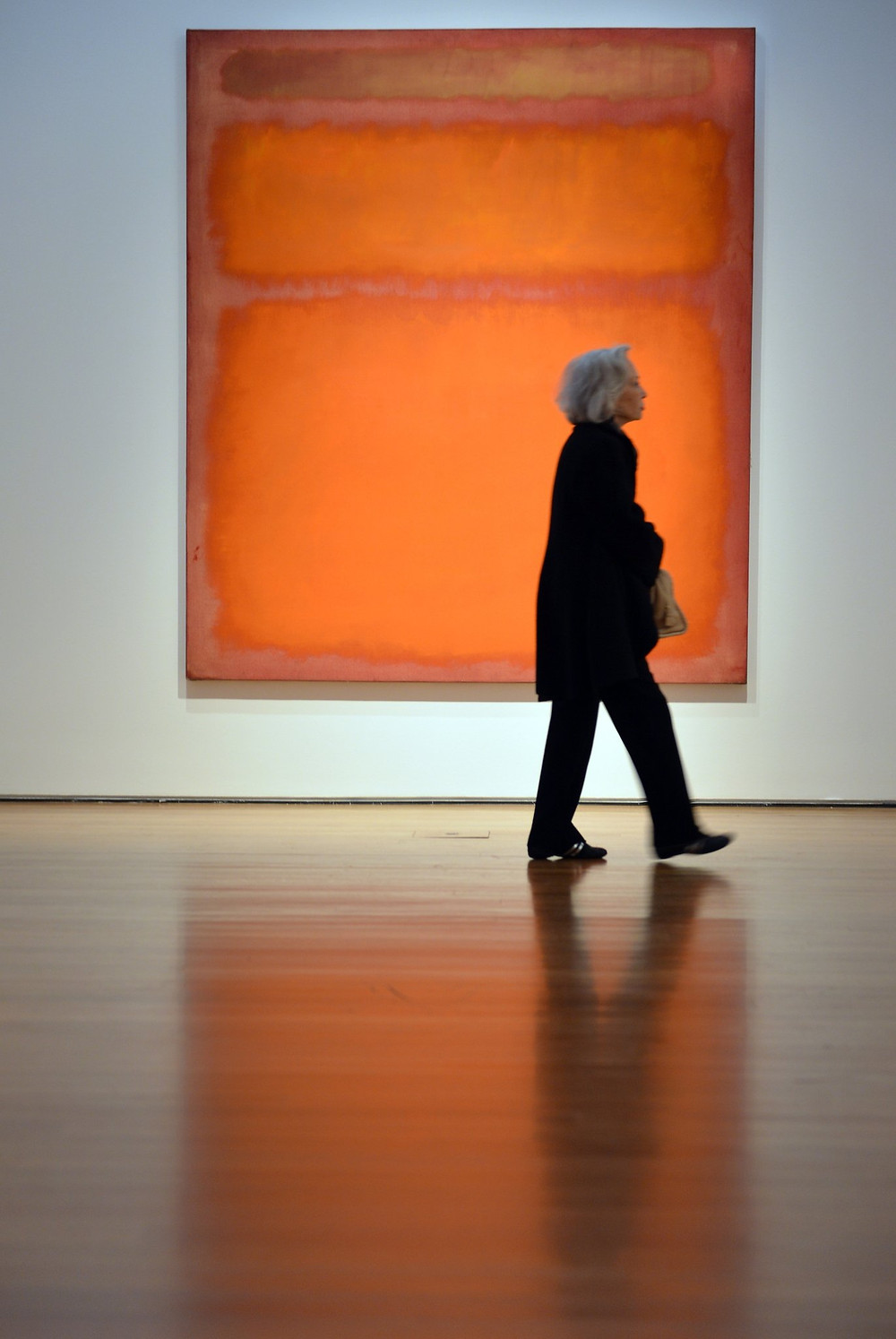 A woman walks past a Rothko abstract painting
