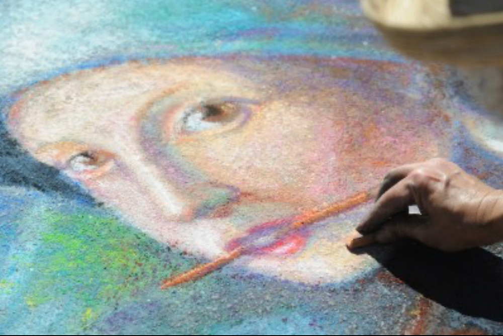 Close-up of a portrait of a woman painted on a sidewalk in pastel.