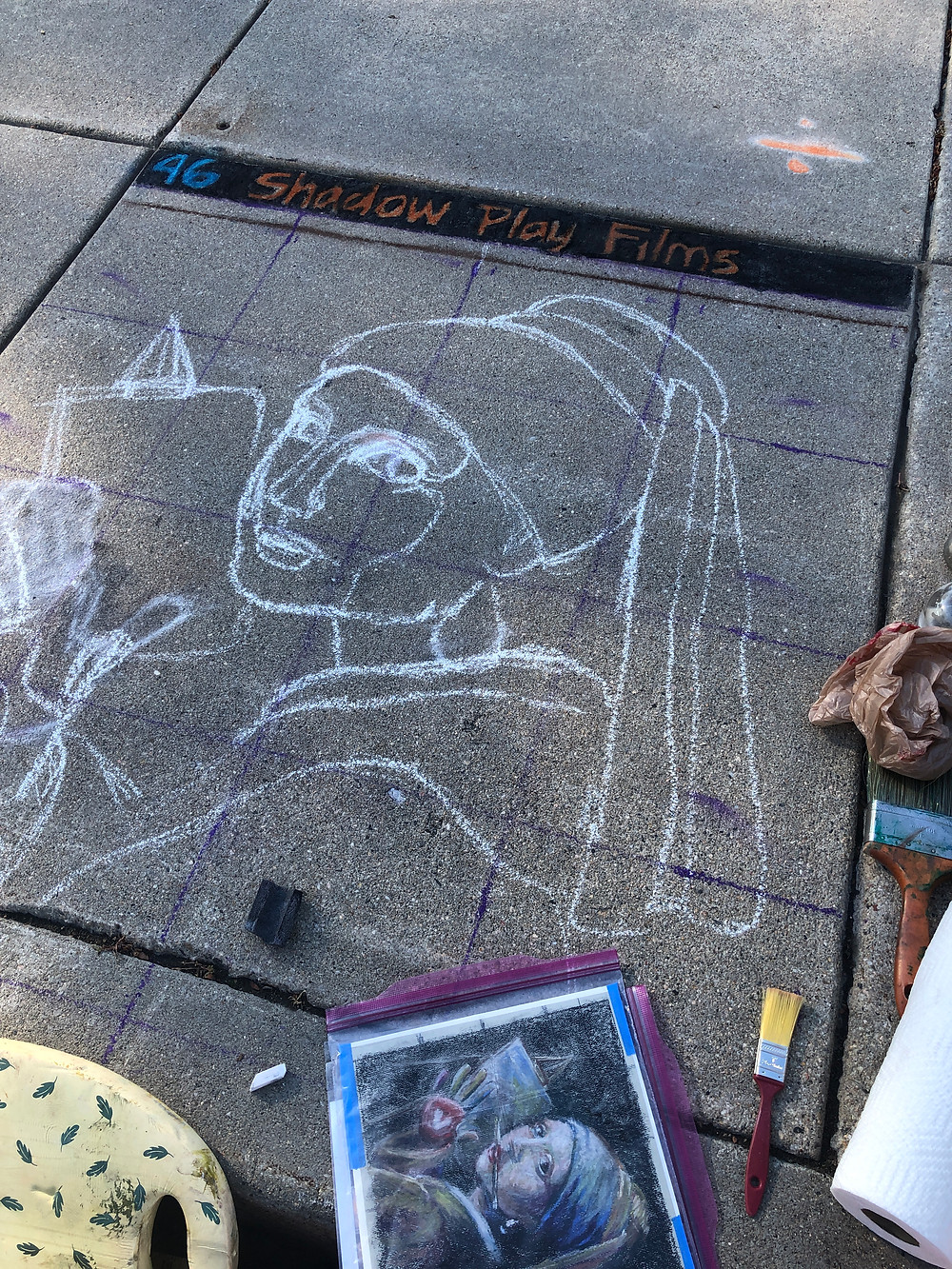 A chalk drawing of Vermeer's Girl with a Pearl Earring on sidewalk