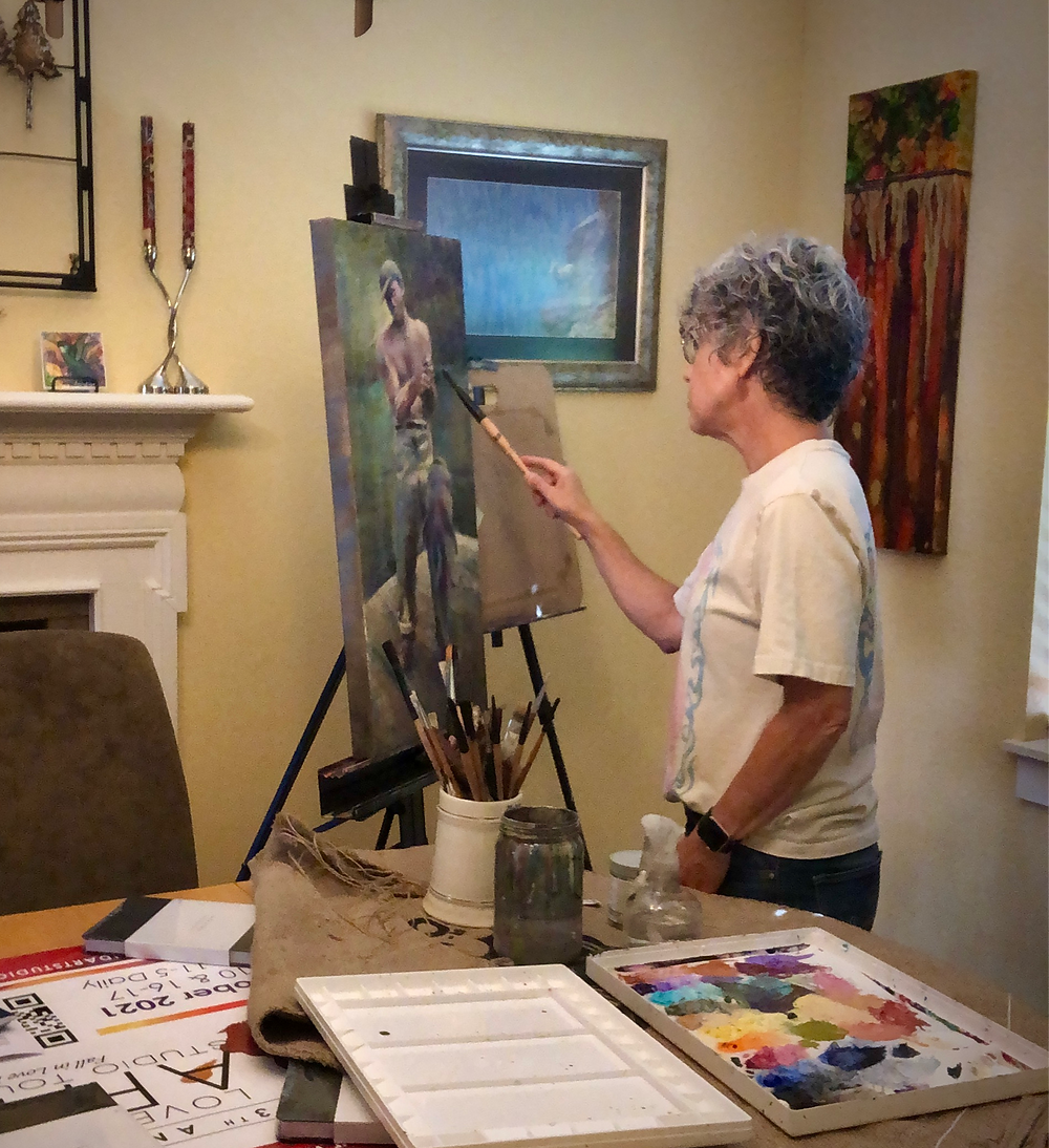 Female artist painting at an easel with palette nearby on table.