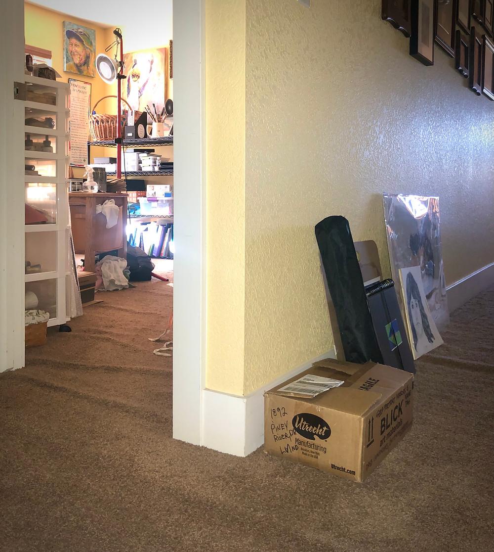 doorway to an art studio, with art supplies in the hallway
