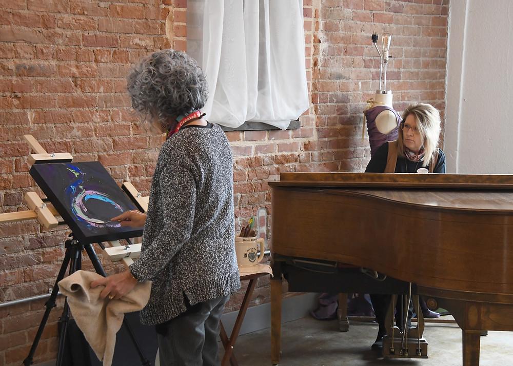 Lisa DuBois painting while Christine James plays piano