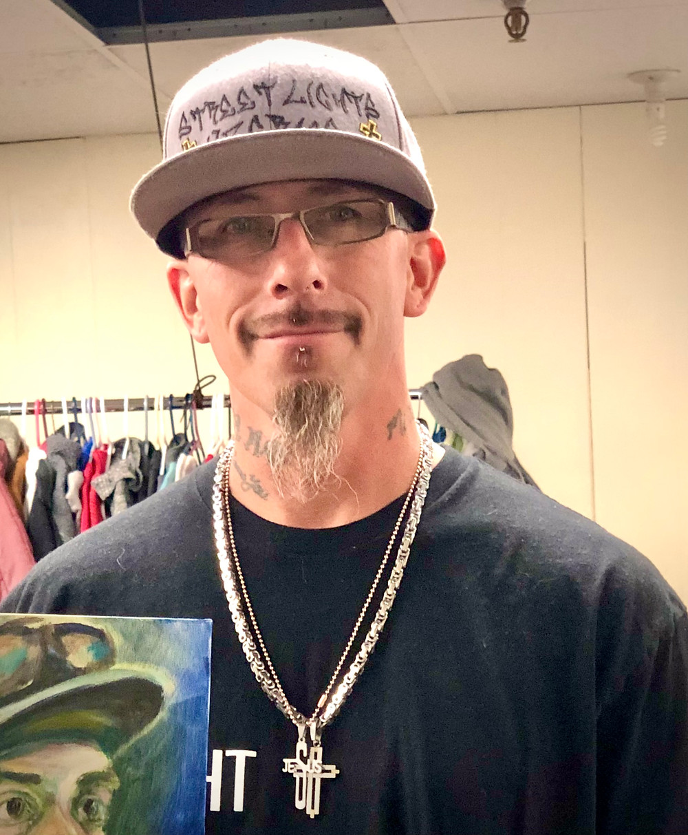Photo of a man wearing a goatee, glasses and ball cap.