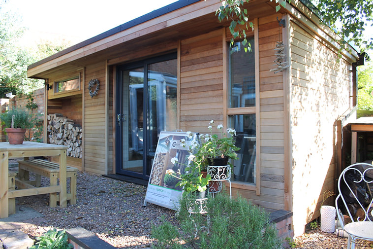 Cedar clad wooden garden room featuring an extension and wood store