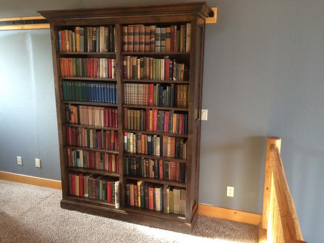 Bookcase on barn-door hardware (closed).
